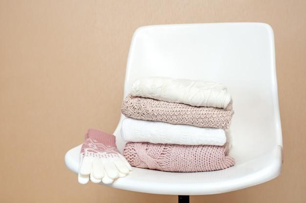 Na białym krześle leży stos dzianych ubrań w zimne dni.