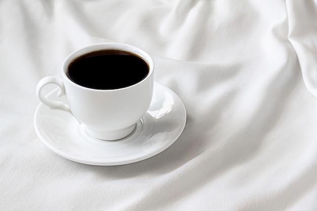 Na białym łóżku stoi biała filiżanka z czarną kawą