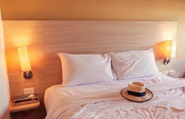 Na białym łóżku w hotelu znajduje się czapka turystyczna.