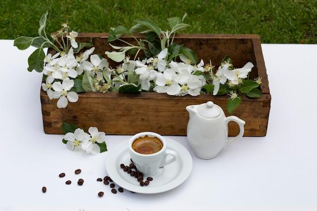 Na białym stole jest stare drewniane pudełko z gałęziami jabłoni, filiżanką kawy