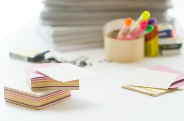Na białym stole kolorowy klocek do notatek na papierze w tle i papeterii