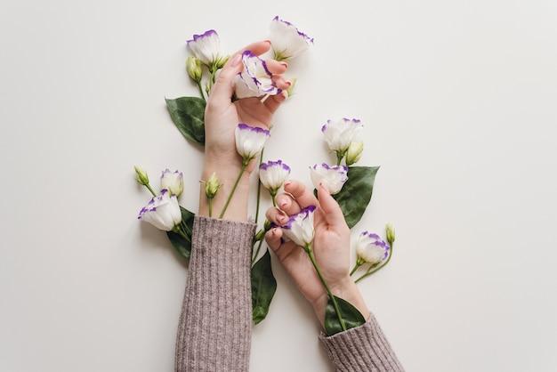 Na białym stole leżą delikatne dłonie i wiosenne kwiaty eustomy