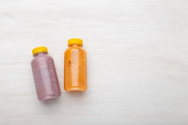 Na białym stole leżą dwie butelki z sokiem pomarańczowym i jagodowym. pojęcie prawidłowego odżywiania i zdrowej przekąski w pracy. przestrzeń reklamowa