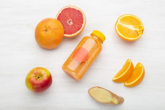 Na białym stole leżą plasterki grejpfruta oraz soku pomarańczowo-pomarańczowego z imbirem i jabłkiem. koncepcja wegetariańskiego śniadania i detoksykacji.