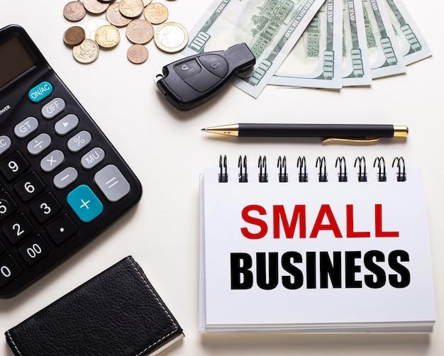 Na białym stoliku kalkulator, kluczyk do auta, gotówka, długopis i notes z napisem small business