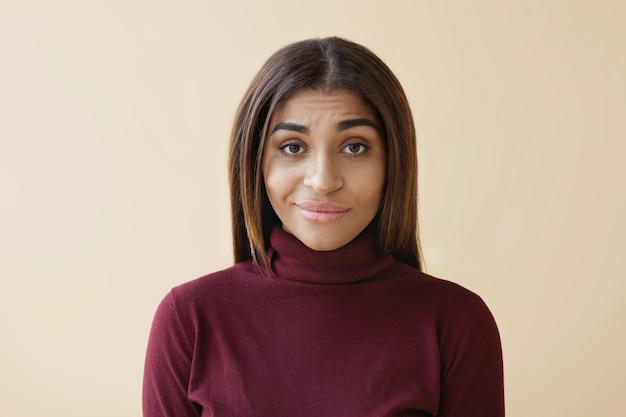 Na białym tle atrakcyjna, sceptyczna młoda brunetka rasy mieszanej, ubrana w stylowy bordowy sweter z golfem, mająca zdezorientowany niepewny wygląd, wyrażający swoje wahania i wątpliwości