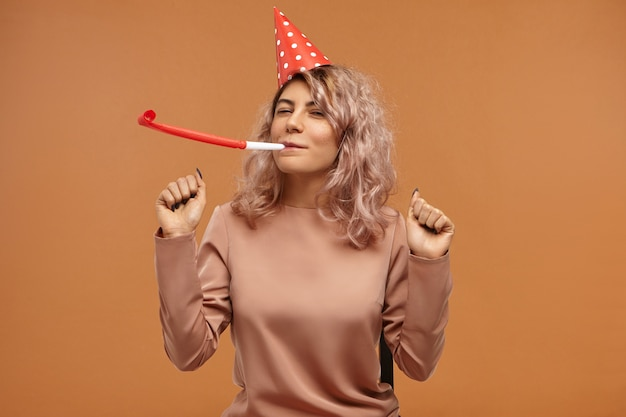 Na białym tle atrakcyjna wesoła szczęśliwa młoda kobieta ubrana w stylowy top i czerwoną czapkę stożkową, dmuchająca w gwizdek i tańcząca, ciesząc się wyrazem twarzy, obchodzi urodziny