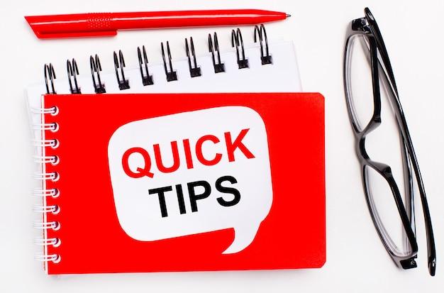 Na białym tle biało-czerwone notesy, czarne okulary, czerwony długopis i biała kartka z napisem szybkie wskazówki