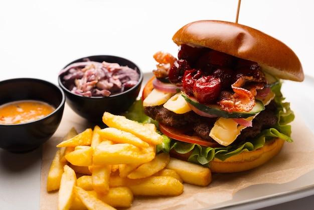 Na białym tle bliska zdjęcie dużego pysznego burgera z przekąskami i frytkami na talerzu.