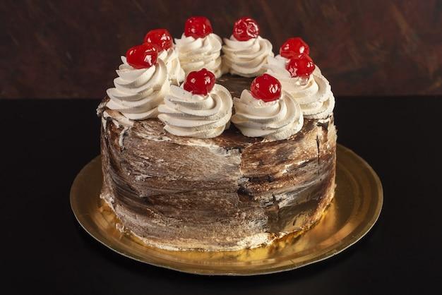 Na białym tle brązowe ciasto z biało-czerwonymi dodatkami na czarnym stole