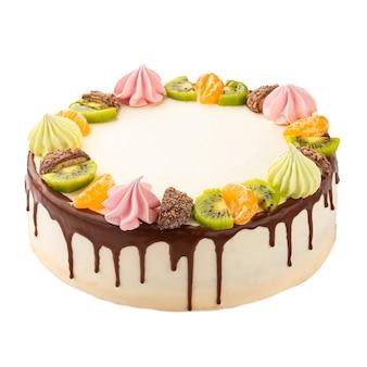 Na białym tle ciasto ozdobione owocami i ciasteczkami na białej powierzchni