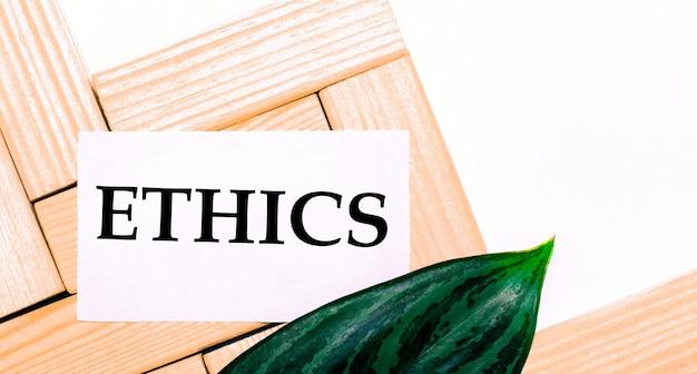 Na białym tle drewniane klocki, biała kartka z napisem etyka i zielony liść rośliny. szablon. widok z góry