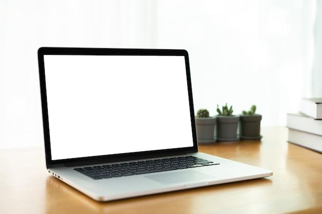 Na białym tle ekran komputera przenośnego ze ścieżką przycinającą, minimalistyczny nowoczesny styl przestrzeni roboczej w domu z laptopem, książkami i rośliną dekoracyjną, w tym kaktus i monstera obliqua.