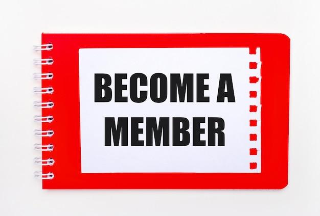 Na białym tle - jasnoczerwony notatnik na spirali. na nim biała kartka papieru z napisem zostań członkiem