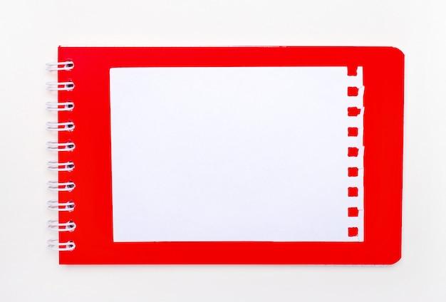 Na białym tle jest jasnoczerwony notatnik w spirali. powyżej znajduje się biała pusta kartka papieru z miejscem na wstawienie tekstu. szablon