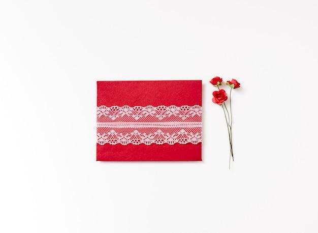 Na białym tle koperta papierowa z koronki i roze na białym tle z miejsca na kopię