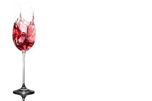 Na białym tle kubek wina z rozpryskiwaniem lodu