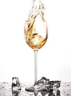 Na białym tle kubek z białego wina i rozpryskiwania lodu