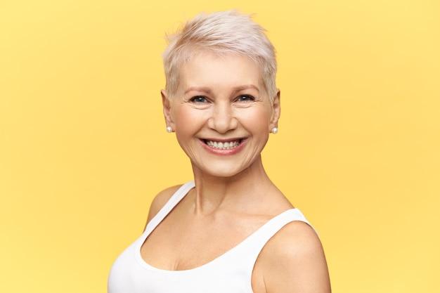 Na białym tle obraz atrakcyjnej kobiety na emeryturze z stylową fryzurą pixie będąc w dobrym nastroju, uśmiechając się szeroko do kamery na sobie kolczyki i biały podkoszulek.