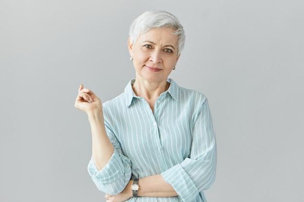 Na białym tle obraz eleganckiej modnej europejskiej kobiety w średnim wieku na emeryturze, pozowanie na sobie stylową niebieską koszulę w paski i zegarek na rękę, mając dobry dzień, uśmiechając się radośnie