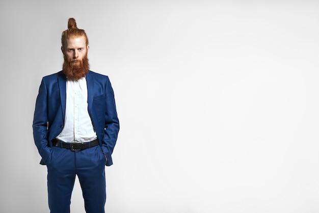 Na białym tle obraz odnoszącego sukcesy modnego młodego biznesmena z węzłem włosów i modną brodą o poważnym wyglądzie pewności siebie, trzymając obie ręce w kieszeniach swojego stylowego stroju. sukces i kariera