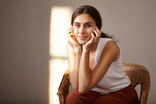 Na białym tle obraz ślicznej tajemniczej młodej kobiety w białej bluzce bez rękawów, spędzającej czas w pomieszczeniu, trzymając ręce na twarzy, z uroczym radosnym uśmiechem, siedzącą w fotelu o złotej godzinie