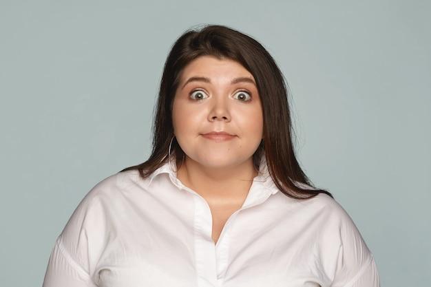 Na białym tle obraz śmiesznej menadżerki plus size w białej koszuli, wyrażającej zdziwienie, wpatrującej się z niedowierzaniem, zszokowanej niespodziewanymi wiadomościami lub plotkami. zaskoczenie i szok