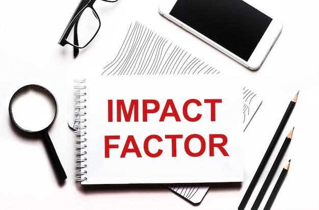 Na białym tle okulary, lupa, ołówki, smartfon i notatnik z napisem impact factor