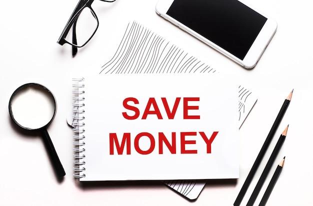 Na białym tle okulary, lupa, ołówki, smartfon i notatnik z napisem oszczędzaj pieniądze