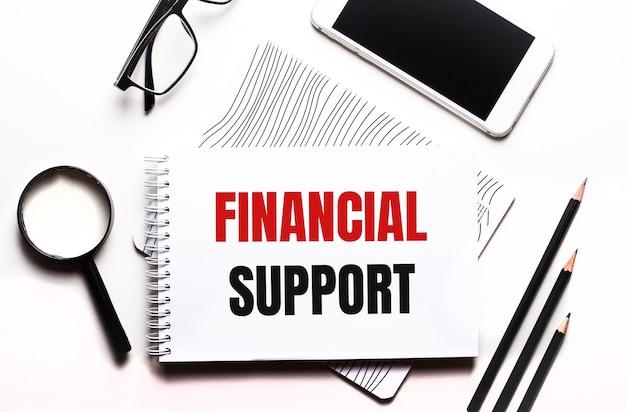 Na białym tle okulary, lupa, ołówki, smartfon i notatnik z napisem wsparcie finansowe