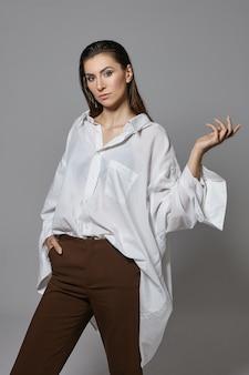 Na białym tle pionowe ujęcie stylowej młodej brunetki w modnych ubraniach o poważnym, pewnym wyrazie twarzy, gestykulującej, jakby trzymała coś w otwartej dłoni. styl, moda i uroda