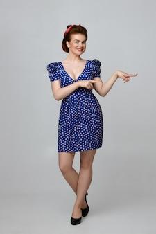 Na białym tle pionowy portret pełnej długości wesoła piękna młoda kaukaski dziewczyna pin up w sukience vintage, uśmiechając się radośnie, reklamując jakiś produkt, wskazując palce wskazujące