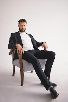 Na białym tle pionowy portret udanego przystojnego, stylowego, młodego szefa europejskiego mężczyzny z rozmytą, przyciętą brodą, ubrany w modne męskie stroje, relaksując się w fotelu i patrząc z poważnym spojrzeniem