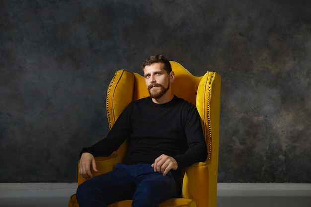 Na białym tle portret dobrze wyglądającego eleganckiego młodego europejczyka z rozmytą, przyciętą brodą i wąsami, ubrany w stylowe czarne ubrania, pozowanie, siedząc sam w wygodnym żółtym fotelu