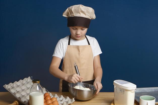 Na białym tle portret ładny nastoletniego chłopca, ucząc się robić ciasteczka w warsztatach kulinarnych