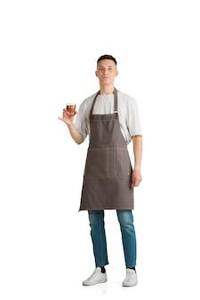 Na białym tle portret młodego mężczyzny kaukaski barista lub barman w brązowym fartuchu uśmiecha się