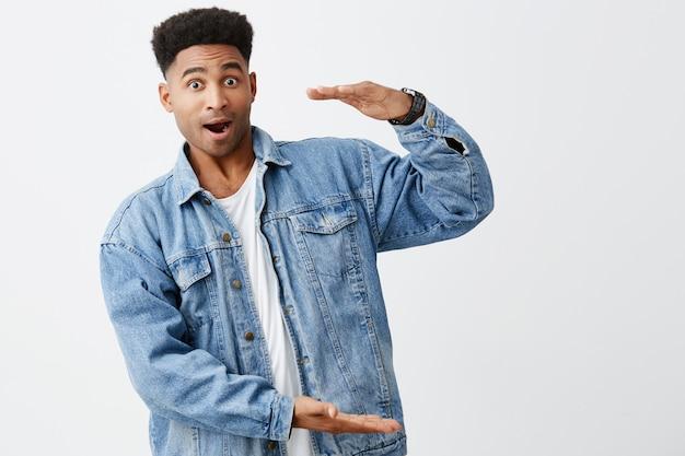 Na białym tle portret młodego śmiesznego ciemnoskórego mężczyzny z fryzurą afro w swobodnej białej koszuli pod jeansową kurtką udającą, że trzyma duże pudełko w rękach z podekscytowanym wyrazem twarzy