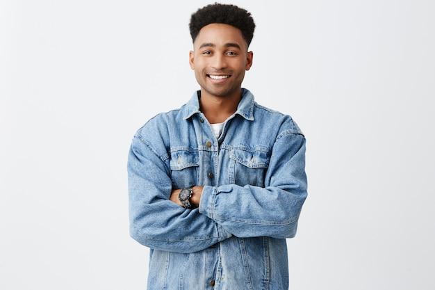 Na białym tle portret młodego śmiesznego ciemnoskórego mężczyzny z rękami skrzyżowanymi z fryzurą afro w swobodnej białej koszuli pod jeansową kurtką z wyrazem podekscytowanej twarzy