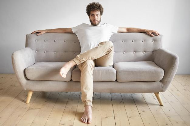 Na białym tle portret modnego, modnie wyglądającego młodego europejczyka z grubą brodą odpoczywającego w domu, siedzącego niedbale na luksusowej kanapie, oglądającego telewizję, zrelaksowanego. ludzie, styl życia i wypoczynek