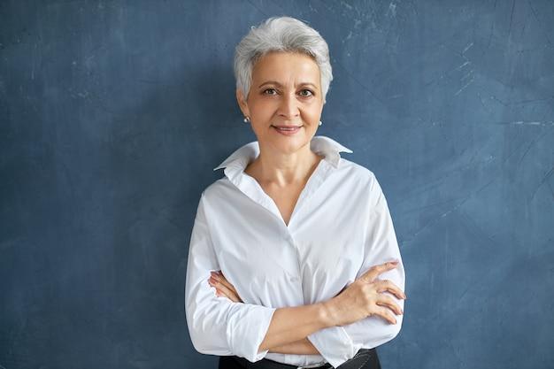 Na białym tle portret stylowej udanej 50-letniej kobiety pośrednika w białej koszuli pozowanie na pustej ścianie