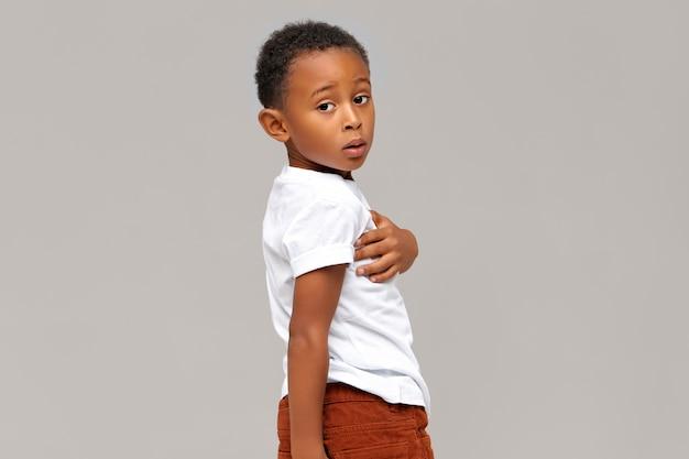 Na białym tle portret zakłopotany ciemnoskóry chłopiec ubrany w białą koszulkę. język ciała