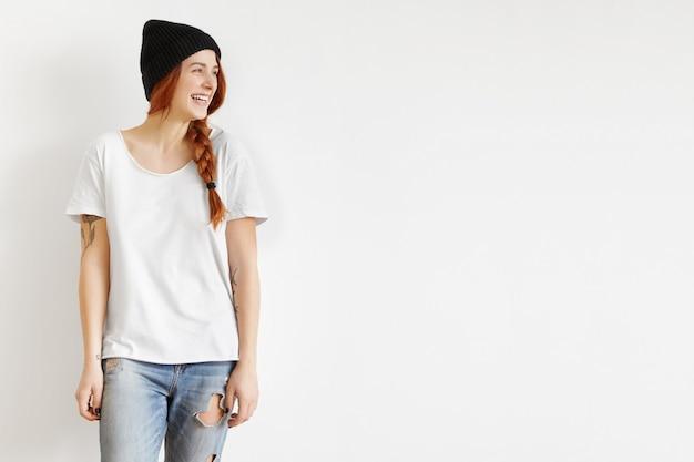 Na białym tle przycięty portret modnej stylowej młodej kobiety modelu na sobie modne ubrania, patrząc od hotelu