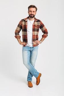 Na białym tle przystojny brodaty mężczyzna w stroju hipster, ubrany w dżinsy