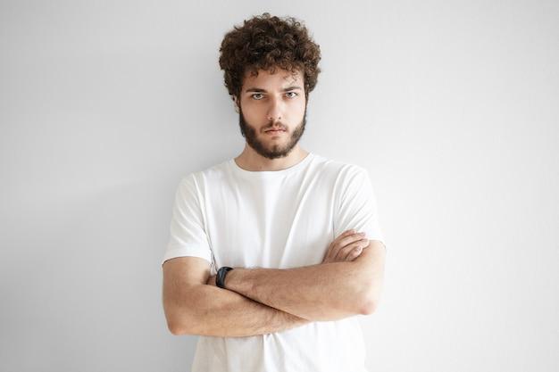 Na białym tle przystojny młody niechętny mężczyzna ze stylową fryzurą i zarostem, wyrażający dezaprobatę lub brak szacunku, z ponurym spojrzeniem, trzymając ręce skrzyżowane na piersi