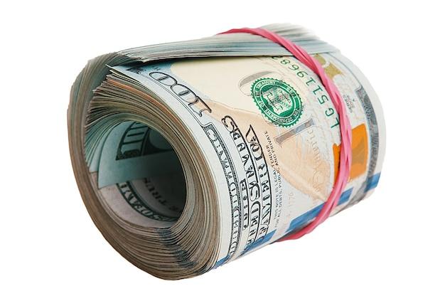 Na białym tle rolka dolarów. na białej powierzchni leży duży zwój banknotów stu dolarowych.