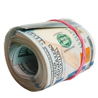 Na białym tle rolka dolarów. na białej ścianie leży duża rolka banknotów stu dolarowych.