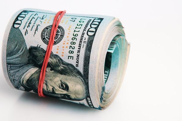 Na białym tle rolka dolarów. spoczywa duża rolka banknotów stu dolarowych