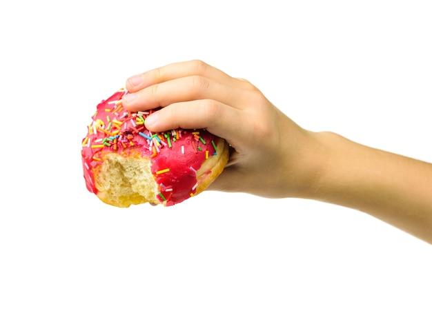 Na białym tle różowy pączek w dłoni dziecka z odgryzioną krawędzią. słodycze cukiernicze.