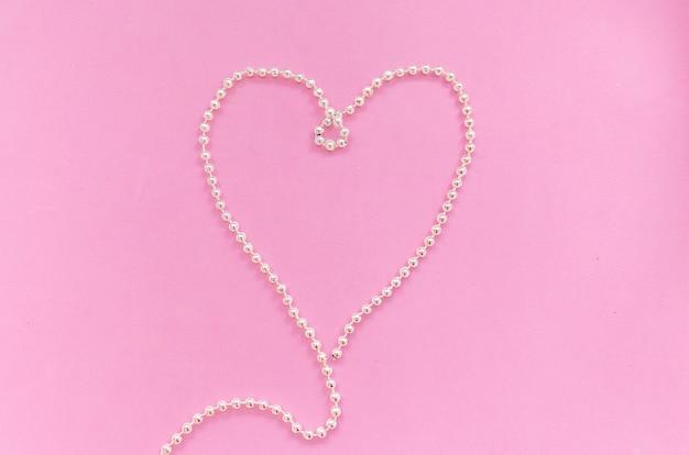 Na białym tle srebrny naszyjnik z koralików w kształcie serca na różowym tle widok z góry, walentynki, dzień zakochanych