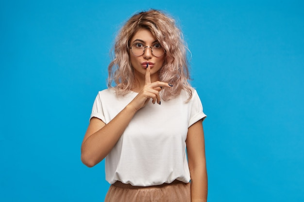 Na białym tle strzał piękna studentka dziewczyna z różowawymi włosami, chowając palec na ustach, prosząc o ciszę, przygotowując się do egzaminów